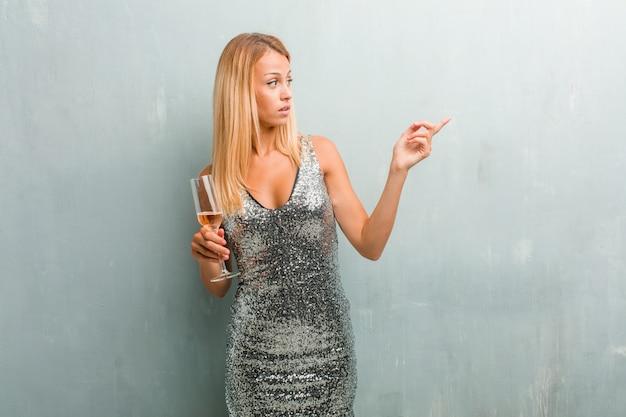 Portrait de jeune femme blonde élégante pointant sur le côté, souriant surpris de présenter quelque chose de naturel et décontracté. tenant un verre de champagne. Photo Premium