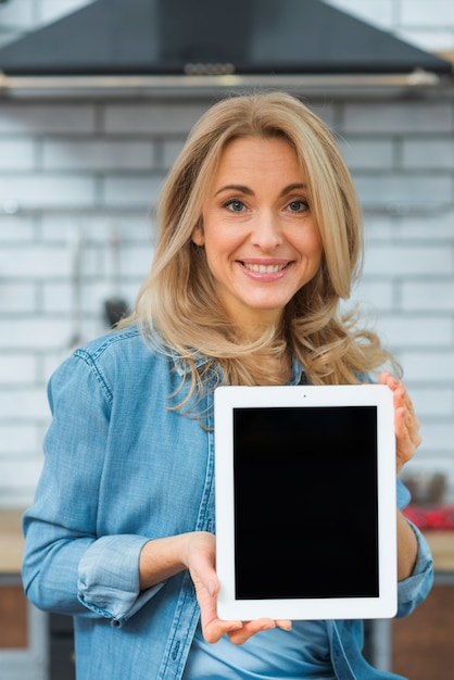 Portrait d'une jeune femme blonde montrant une tablette numérique Photo gratuit
