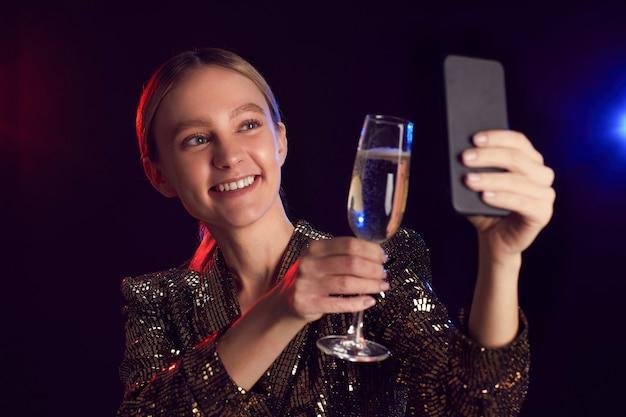 Portrait De Jeune Femme Blonde Prenant Selfie Photo Via Smartphone Tout En Profitant De La Fête En Boîte De Nuit Et Grillage Avec Verre De Champagne Photo Premium