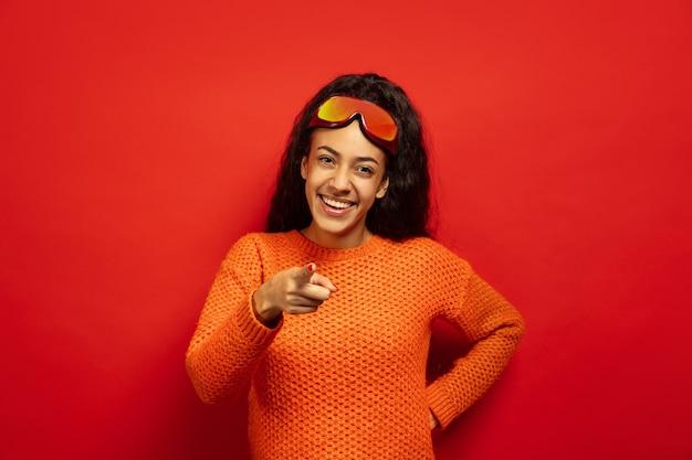 Portrait De Jeune Femme Brune Afro-américaine En Masque De Ski Sur L'espace Rouge Photo gratuit