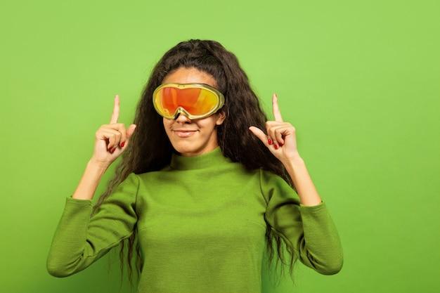 Portrait De Jeune Femme Brune Afro-américaine En Masque De Ski Sur Fond Vert Studio. Concept D'émotions Humaines, Expression Faciale, Ventes, Publicité, Sports D'hiver Et Vacances. Souriant, Pointant Vers Le Haut. Photo gratuit