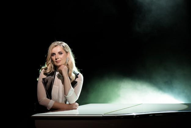 Portrait de jeune femme caucasienne, debout près du piano à queue Photo Premium