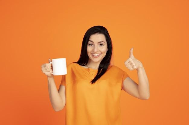 Portrait De Jeune Femme Caucasienne Sur Fond De Studio Orange. Beau Modèle Femme Brune En Chemise. Concept D'émotions Humaines, Expression Faciale, Ventes, Publicité. Copyspace. Boire Du Café Ou Du Thé. Photo gratuit