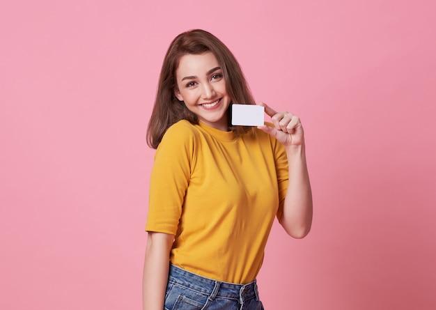 Portrait d'une jeune femme en chemise jaune montrant la carte de crédit et en regardant loin dans l'espace de copie isolé sur rose. Photo Premium