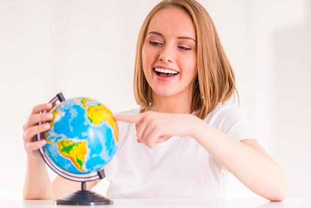 Portrait d'une jeune femme choisit une place sur le globe. Photo Premium