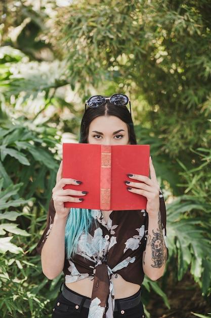 Portrait, jeune, femme, couverture, bouche, livre rouge Photo gratuit