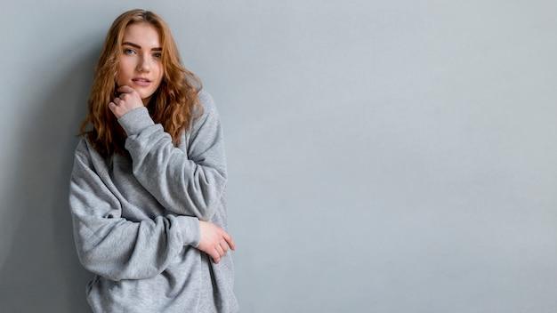 Portrait, jeune, femme, debout, contre, mur gris Photo gratuit
