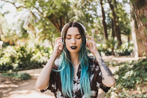 Portrait d'une jeune femme écoutant de la musique sur un casque Photo gratuit