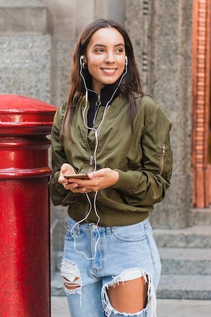 Portrait, de, a, jeune femme, écoute, musique, sur, écouteur, via, téléphone portable Photo gratuit