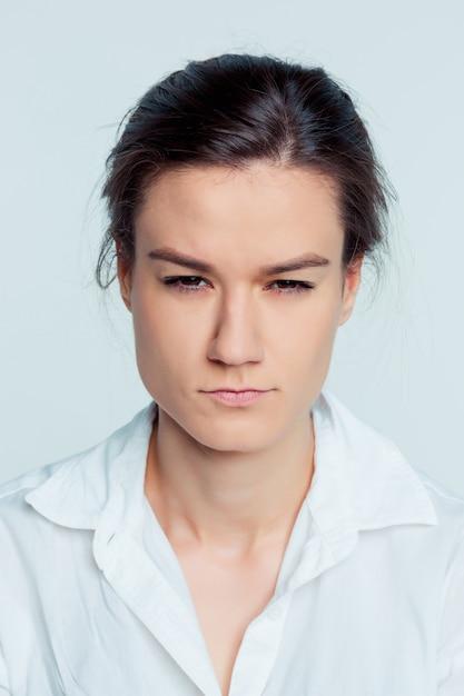 Le Portrait De La Jeune Femme Avec Des émotions Réfléchies Sur L'espace Bleu Photo gratuit