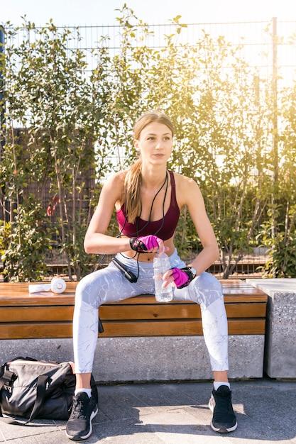 Portrait d'une jeune femme fitness assis sur un banc en ouvrant la bouteille d'eau Photo gratuit