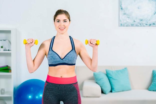Portrait d'une jeune femme heureuse exerçant avec des haltères jaunes à la maison Photo gratuit