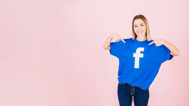 Portrait d'une jeune femme heureuse pointant sur son t-shirt avec l'icône facebook Photo gratuit
