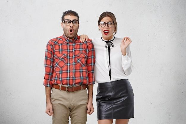 Portrait De Jeune Femme Et Homme Perplexe Choqué Dans Des Lunettes, Des Vêtements Formels Découvrir Des Nouvelles Désagréables Ou Terribles Photo gratuit