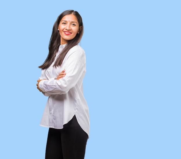 Portrait d'une jeune femme indienne croisant ses bras, souriante et heureuse, confiante et amicale Photo Premium