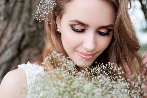 Portrait de jeune femme jolie en robe de mariée blanche à l'extérieur Photo Premium
