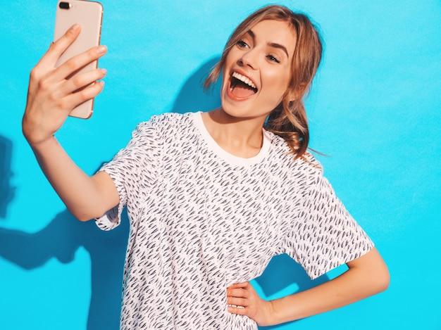 Portrait De Jeune Femme Joyeuse Prenant Selfie Photo. Belle Fille Tenant La Caméra Du Smartphone. Modèle Souriant Posant Près Du Mur Bleu En Studio. Modèle Surpris Choqué Photo gratuit