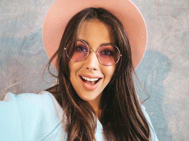 Portrait De Jeune Femme Joyeuse Prenant Selfie Photo Avec Inspiration Et Portant Des Vêtements Modernes Et Un Chapeau. Photo gratuit