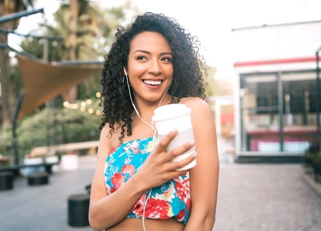 Portrait De Jeune Femme Latine Afro-américaine, écouter De La Musique Avec Des écouteurs Tout En Tenant Une Tasse De Café à L'extérieur Dans La Rue. Photo Premium
