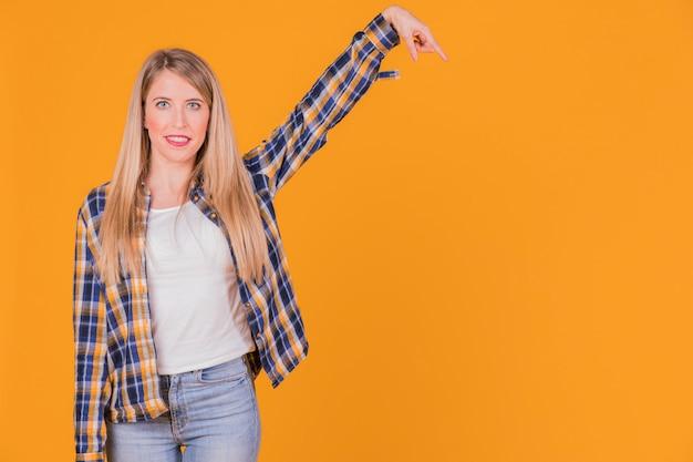 Portrait, jeune, femme, levée bras, contre, orange, toile de fond Photo gratuit