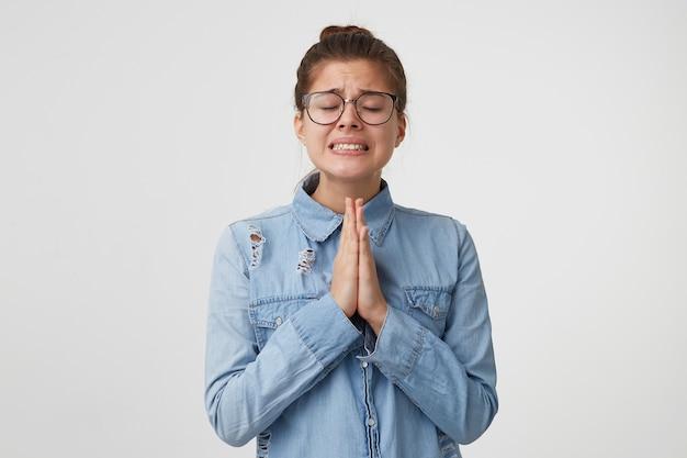 Portrait De Jeune Femme à Lunettes Se Tient Avec Les Yeux Fermés, Les Mains Jointes Devant Elle Photo gratuit