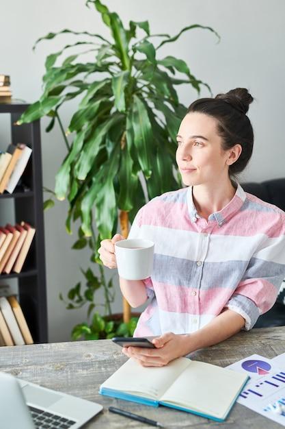 Portrait De Jeune Femme Moderne Bénéficiant D'un Café Tout En Travaillant à Domicile, Copiez L'espace Photo Premium