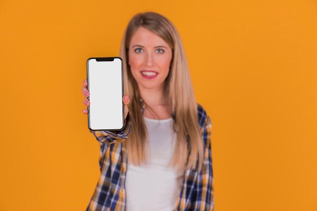 Portrait d'une jeune femme montrant son téléphone portable sur fond orange Photo gratuit