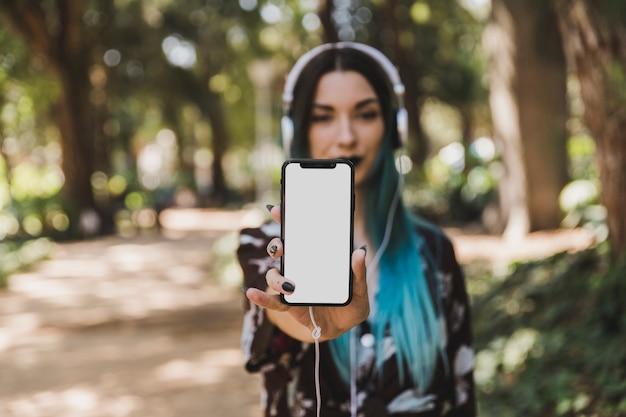 Portrait de jeune femme montrant un téléphone intelligent blanc blanc Photo gratuit