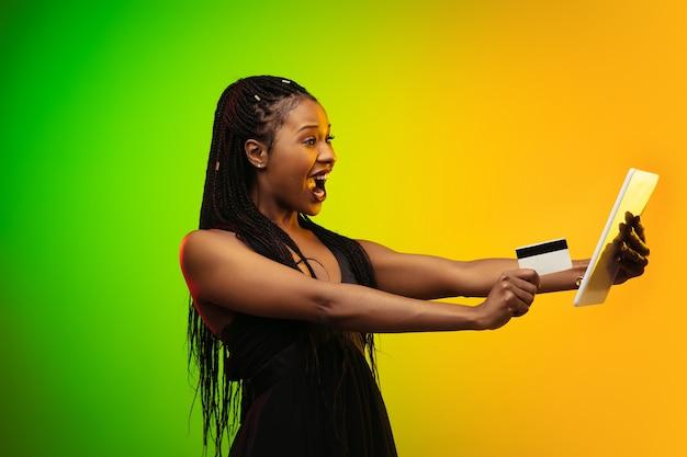 Portrait De Jeune Femme En Néon Sur Fond Dégradé. Rire Et Tenir Une Tablette Et Une Carte De Crédit. Photo gratuit