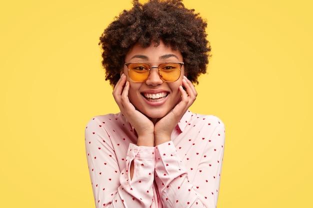 Portrait De Jeune Femme Noire Heureuse A Un Sourire Tendre à Pleines Dents Agréable, Tient Le Menton Photo gratuit