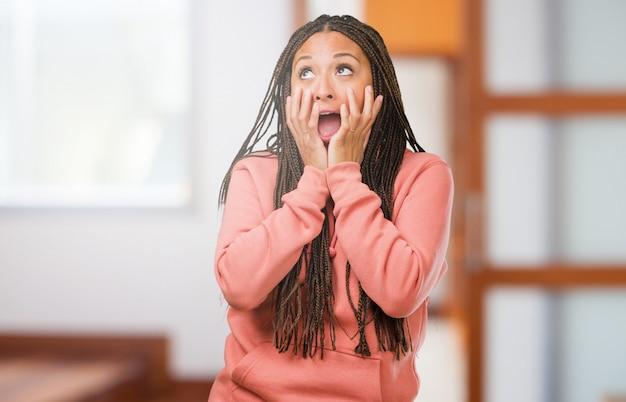 Portrait d'une jeune femme noire portant des tresses très effrayée et effrayée, désespérée pour quelque chose Photo Premium