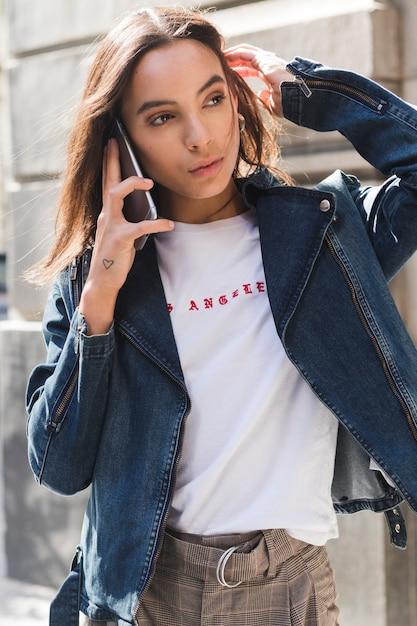 Portrait d'une jeune femme parlant sur un téléphone mobile en plein air Photo gratuit