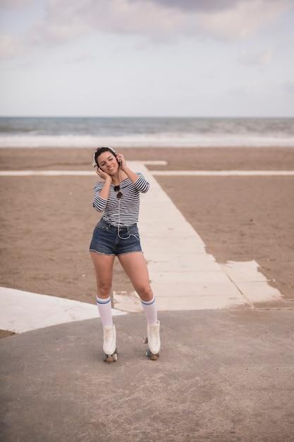 Portrait, de, a, jeune femme, patineur, écouter musique sur casque, à, plage Photo gratuit