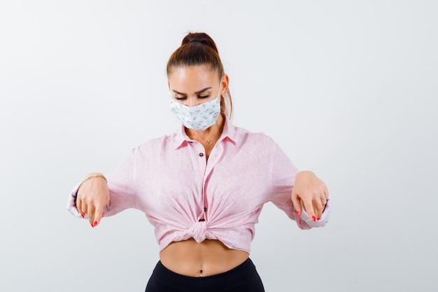 Portrait De Jeune Femme Pointant Vers Le Bas En Chemise, Masque Et à La Vue De Face Ciblée Photo gratuit
