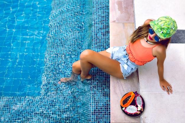 Portrait De Jeune Femme Posant Près De La Piscine Avec Des Fruits Tropicaux Photo gratuit