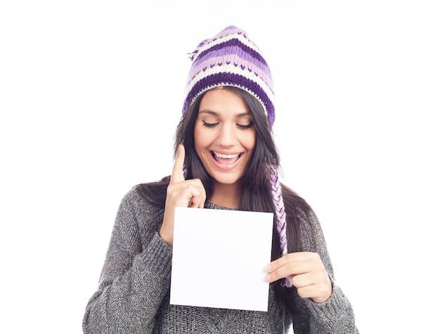 Portrait de jeune femme avec un pull et un chapeau péruvien en laine tenant une carte de signe Photo Premium