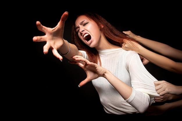 Portrait d'une jeune femme qui, effrayée et effrayée, tente de s'échapper des nombreuses mains qui la tirent en arrière et la déchirent. notion de solitude, perte, peur. portrait effrayant et terrible Photo Premium