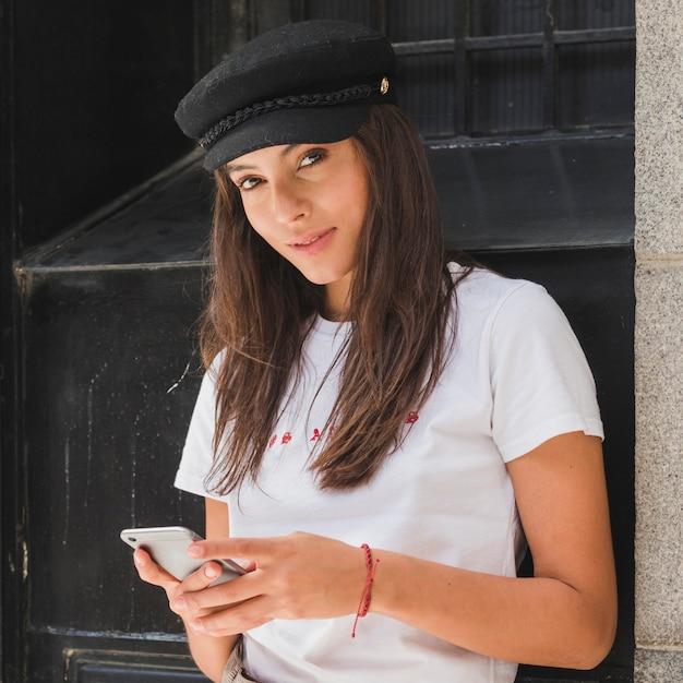 Portrait, jeune, femme, regarder, appareil-photo, utilisation, téléphone portable Photo gratuit