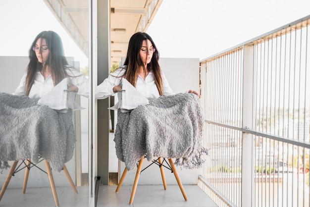 Portrait, jeune, femme, séance, chaise, balcon, tenue, journal Photo gratuit