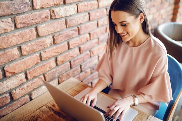 Portrait De Jeune Femme Séduisante, Assis Dans La Cafétéria Et à L'aide D'un Ordinateur Portable Photo Premium