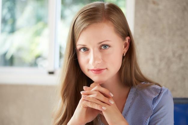 Portrait de jeune femme séduisante, regardant la caméra avec ses mains serrées Photo gratuit