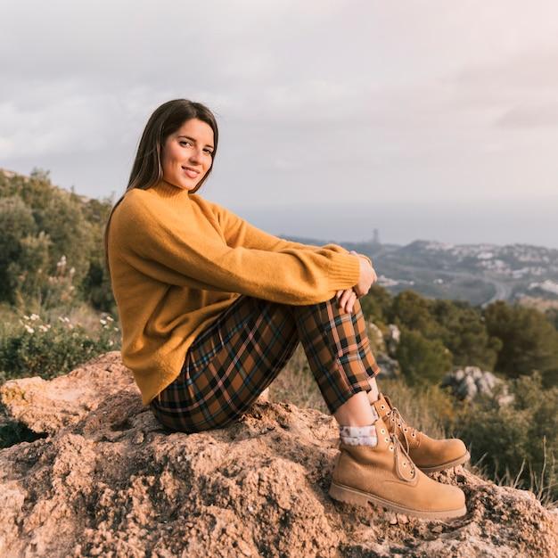 Portrait d'une jeune femme souriante assise au sommet de la montagne en regardant la caméra Photo gratuit