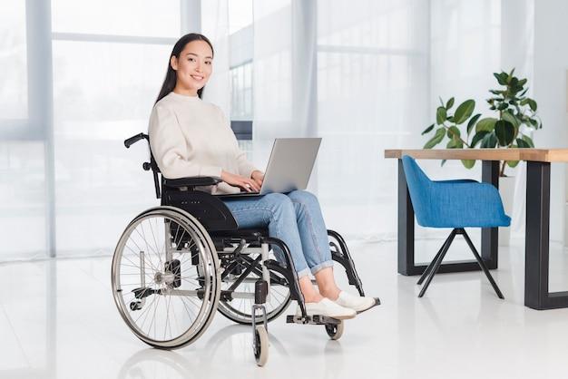 Portrait d'une jeune femme souriante assise sur un fauteuil roulant, regardant la caméra avec un ordinateur portable sur ses genoux Photo gratuit
