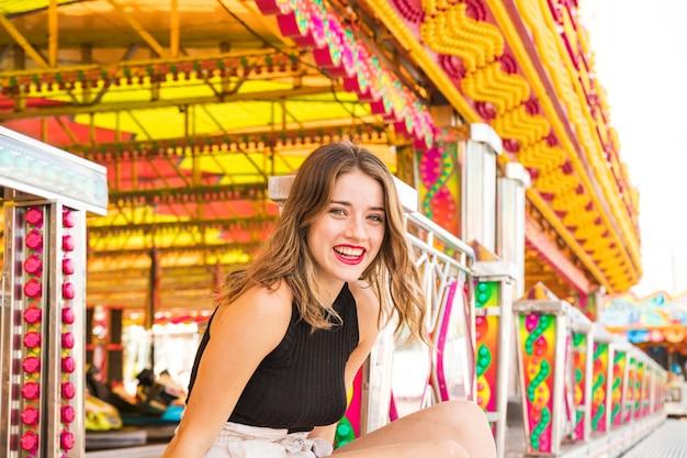 Portrait de jeune femme souriante au parc d'attractions Photo gratuit
