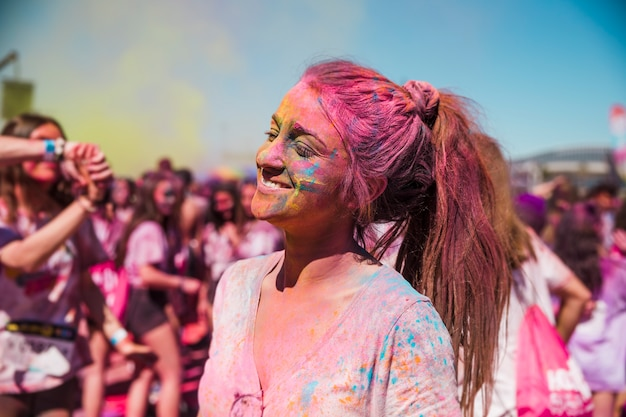 Portrait d'une jeune femme souriante couverte de couleur holi Photo gratuit