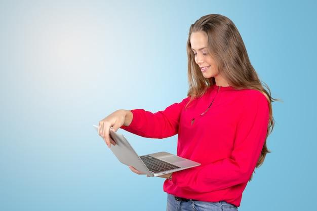 Portrait d'une jeune femme souriante debout avec un ordinateur portable Photo Premium