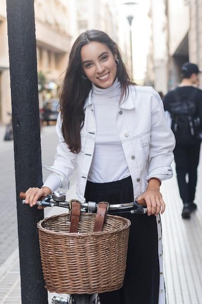 Portrait de jeune femme souriante debout avec son vélo dans la rue Photo gratuit