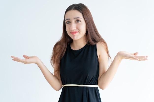 Portrait de jeune femme souriante, haussant les épaules Photo gratuit