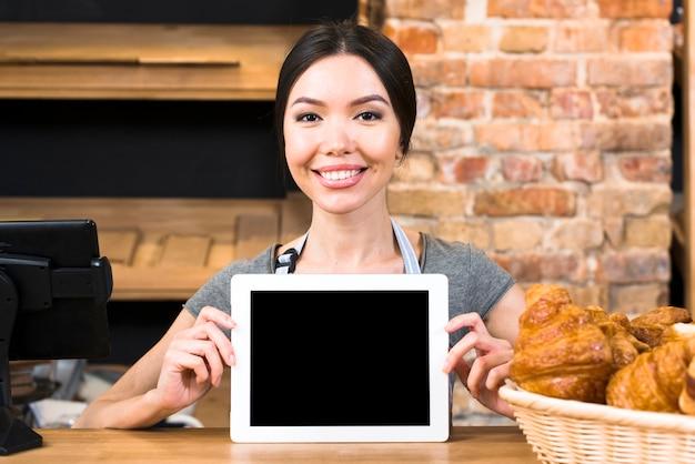 Portrait d'une jeune femme souriante montrant une tablette numérique près du croissant sur le comptoir de la boulangerie Photo gratuit