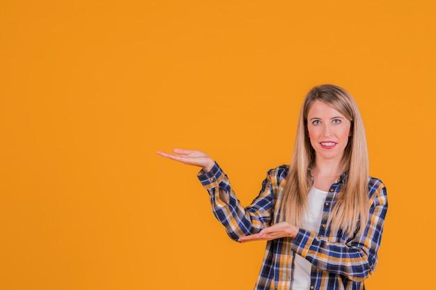Portrait d'une jeune femme souriante présentant quelque chose contre un fond orange Photo gratuit